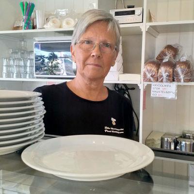 En kvinna med kort hår som står bakom en disk i ett kafé.