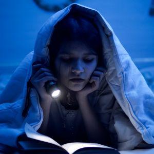 En liten flicka läser med ficklampa under täcket i ett mörkt rum.