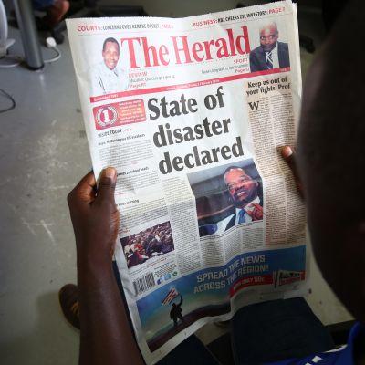 Mies lukee paikallislehdestä Zimbabwen presidentistä, joka julisti maataloustilanteen kansalliseksi katastrofiksi.