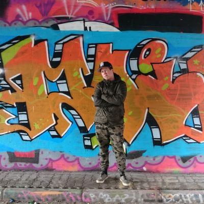 Mikko Könkkölä maalaamansa graffitin edessä.