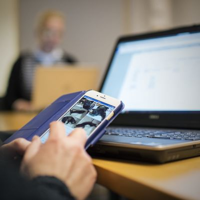 Älypuhelimen käyttöä kokoustilanteessa.