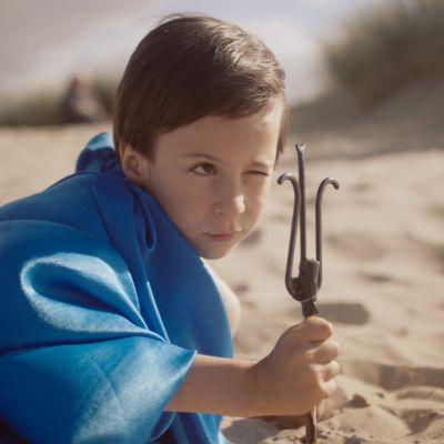 Aatos leikkii Poseidonia ja tähyää pienen atraimen läpi, maaten hiekkarannalla, Reeta Huhtasen dokumenttielokuvassa Aatos ja Amine.