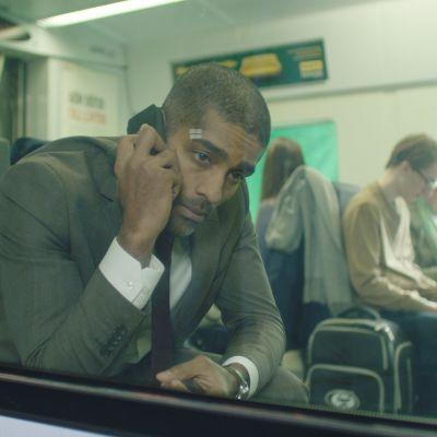 Mies puhuu puhelimeen istuessaan junassa.