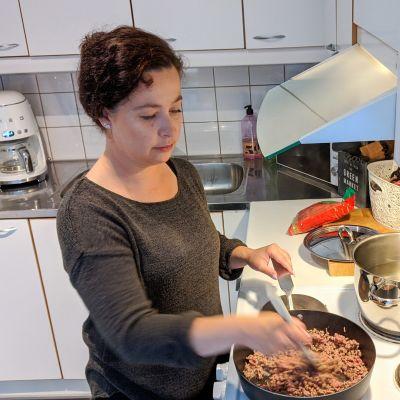 Krista Tapionkaski paistaa jauhelihaa pannulla.