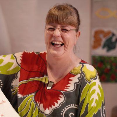 Naurujoogaohjaaja Pia Härkönen nauraa leveästi.