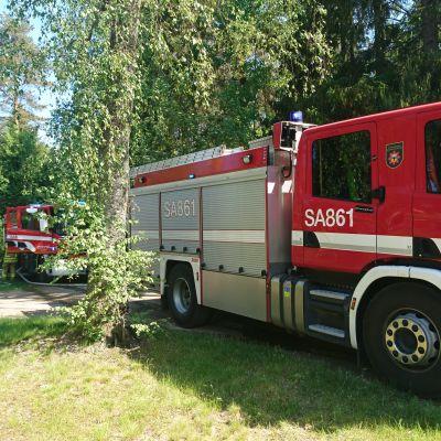 Kaksi paloautoa omakotitalon piha-alueella.