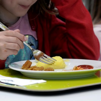 Tyttö haarukoi perunamuussia lautaselta.