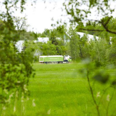 En bil som transporterar avloppsslam vid ett gräsfält. Vid fältet finns träd.