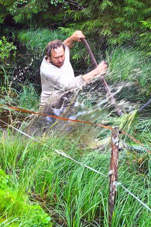 en medelålders manlig ekobonde står i en å med en lie i handen.