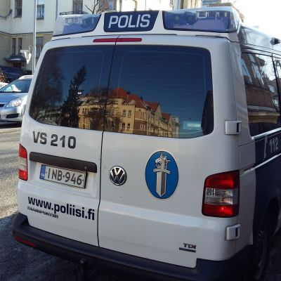 Polisbil parkerad på en gata. I bakfönstret speglas ett hus.