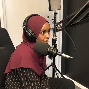 Ung kvinna med hijab och hörlurar i en poddstudio.