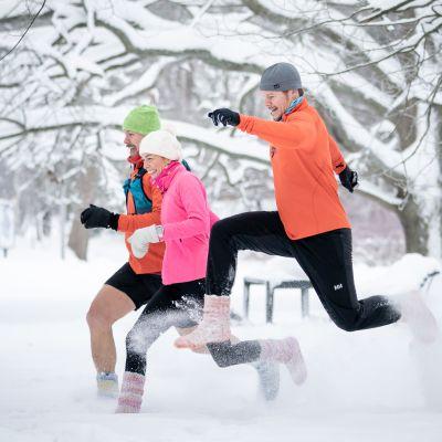 Kolme ihmistä juoksee hangessa jalassaan villasukat. Etummainen ihmisistä on loikannut korkealle ilmaan.