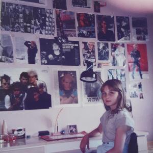 Tyttö kirjoituspöydän äärellä, seinällä kuvia Dingosta.