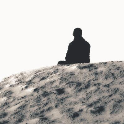 Person sitter ensam på en klippa.