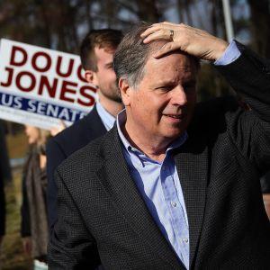Doug Jones framför en supporter som bär skylt med hans namn.