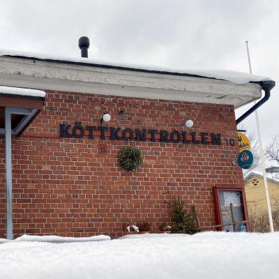 En tegelbyggnad fotad på vintern. På fasaden står det köttkontrollen med stora bokstäver.