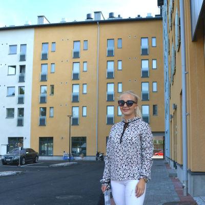 En kvinna i solglasögon står på en innergård framför ett höghus i gult och blått.