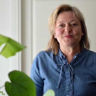 Tina Landén står invid en byrå med en grön växt.