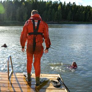 Två män i våtdräkter står på en brygga och tittar på när flera andra simmar.