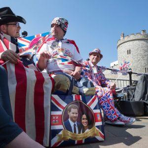 tre män i kläder prydda med storbritanniens färger blått, rött och vitt sitter framför Windsor slott