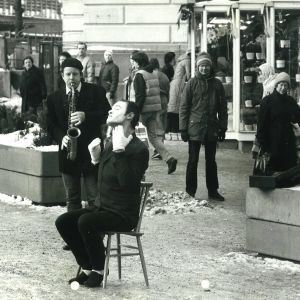 Näyttelijä Tomi Salmela esittää pantomiimia 80-luvun alussa Helsingissä, Timo Eränkö säestää saksofonilla.
