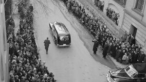 Begravningen av kronprinsessan Märtha. Svart bild med kistan medan folk flockas kring gatan.