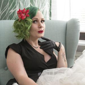 En kvinna med grönt hår och rött läppstift, iklädd en svart klänning, sitter på en ljusgrön fåtölj.