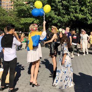 Ung kvinnar hälsar med svenska färger på ballonger och flaggor.