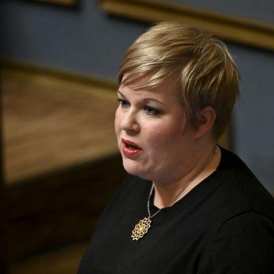 Ljushårig kvinna står och talar. Finansminister Annika Saarikko under riksdagens frågetimme den 21 oktober 2021.