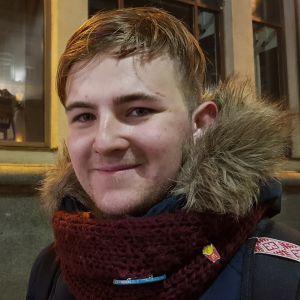 En ung man med kort ljust hår tittar in i kameran och småler. Han har en röd halsduk och en blå jacka med pälsliknande krage.