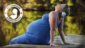 Gravid kvinna sitter på en brygga.