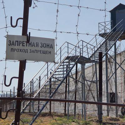 I förgrunden syns taggtråd och stängsel samt en skylt på ryska. Bakom stängslet en trappa i stål som leder upp till ett vakttorn.
