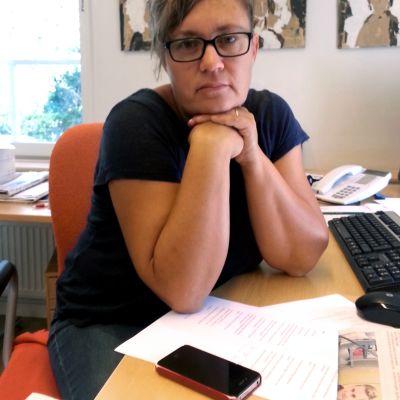 Kansliminister Nina Fellman sitter vid ett skrivbord.