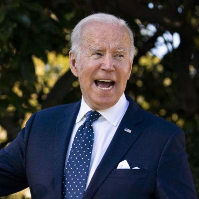 Joe Biden tittar åt sidan och pratar. Han är fotograferad utomhus och är klädd i en mörkblå kostym.