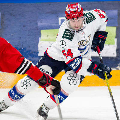 Sebastian Dyk i HIFK:s vita bortatröja driver fram med pucken mot JYP:s Mikko Salmio i röd spelblus.