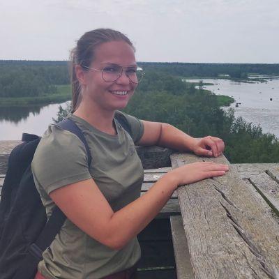Kvinna står uppe i utkikstorn. Hon ler stort. I bakgrunden är hav och skog