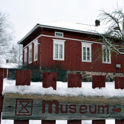 Museiskylt med Ordenshemmet  i bakgrunden.