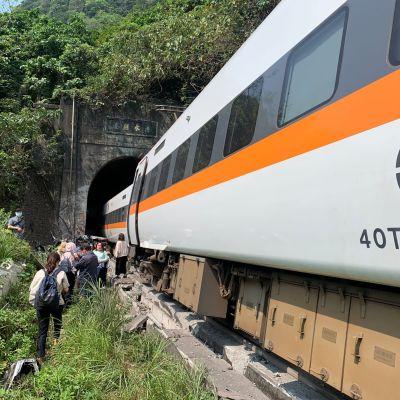 Ett tåg halvvägs inne i en tunnel. Utanför tåget står människor.