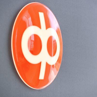 Op:s orange logga på en grå vägg.