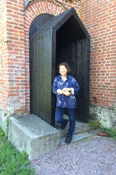 En kvinna i blått vid en dörröppning.