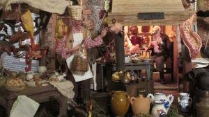 Yksityiskohta roomalaisesta jouluseimestä: ravintola ja ravintolan keittiötä.