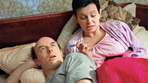 Mies ja nainen makaavat sängyllä. Nainen kirjoittaa vihkoon.
