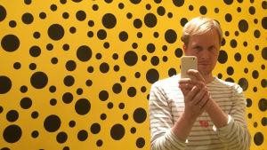 Vaalea mies ja puhelin, tausta kelta-mustapilkkuinen (Yayoi Kusama)