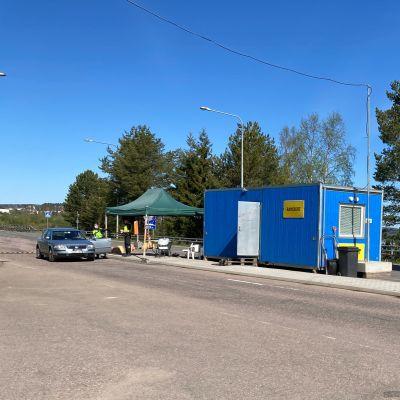 Ylitornion rajanylityspaikka, jossa on sininen kontti, Rajavartiolaitoksen pakettiauto ja telttakatos. Rajanylityspaikalle on pysähtynyt auto, jonka vierellä on kaksi rajatarkastajaa.