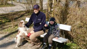 Pappa Liigsoo med sin son och hunden Lotte sitter på en parkbänk i Kuressaare på Ösel i Estland.