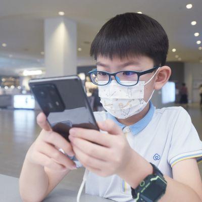 En pojke med glasögon använder en mobiltelefon.