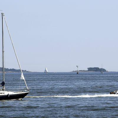 En segelbåt och en motorbåt på havet.