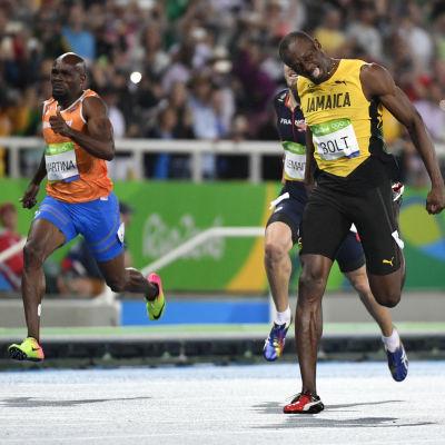 Usain Bolt i gult grinar sig över mållinjen.