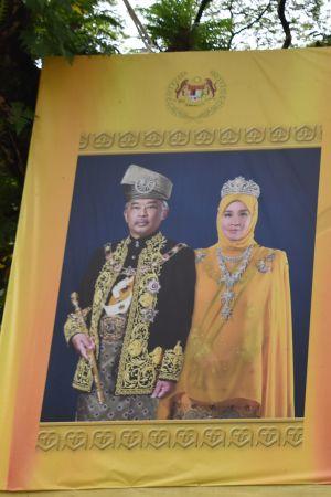 Porträtt av kungen och drottningen kan man se vid vägkanter, på arbetsplatser och i otaliga hem. Klädseln återspeglar deras roll som beskyddare av den malajiska kulturen och av islam.