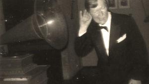 Matti Tuloisela pilailee vanhan gramofonin äänitorven edessä.